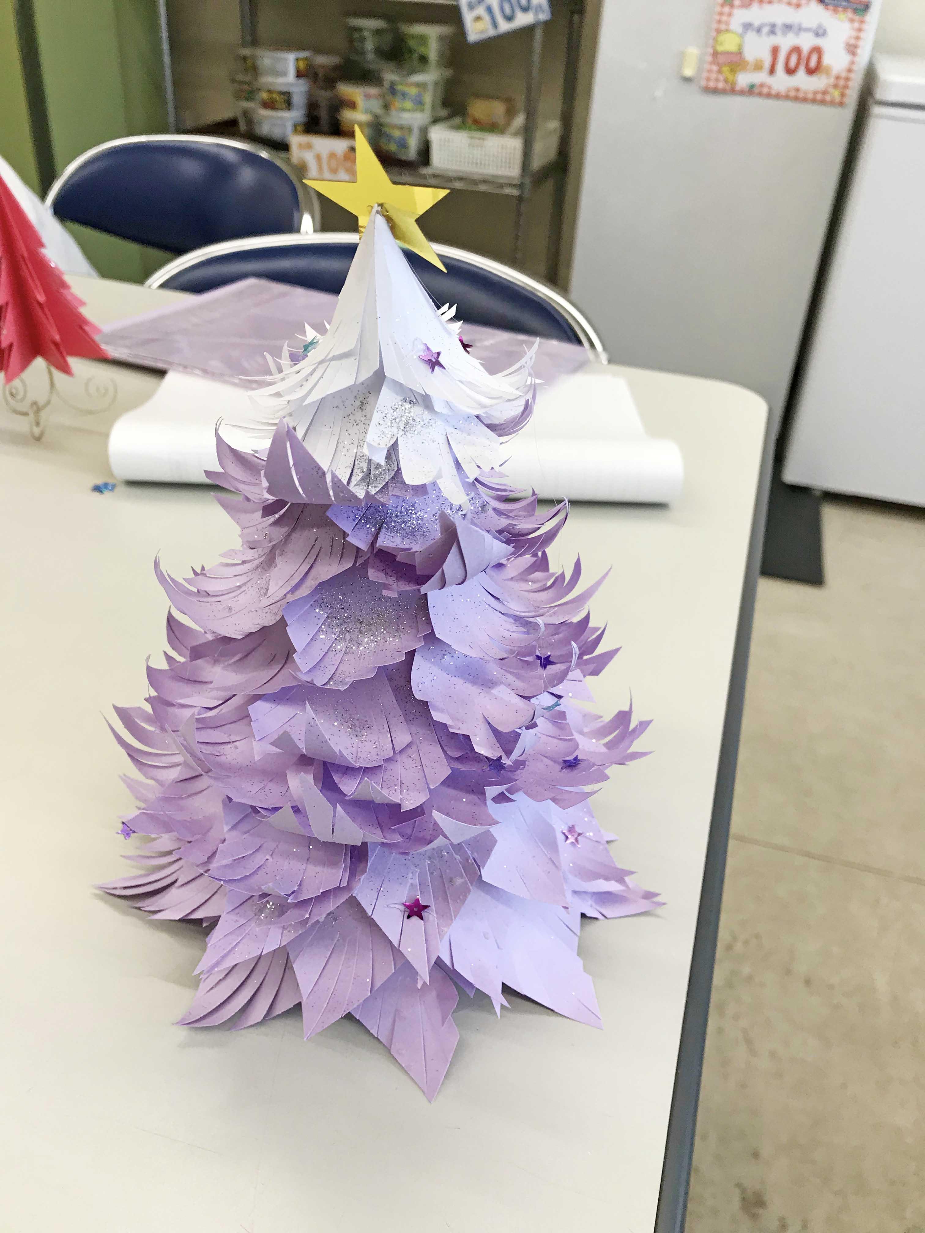 紫の紙片、上部だけ白のクリスマスツリー、頂点には星形の飾り付けが