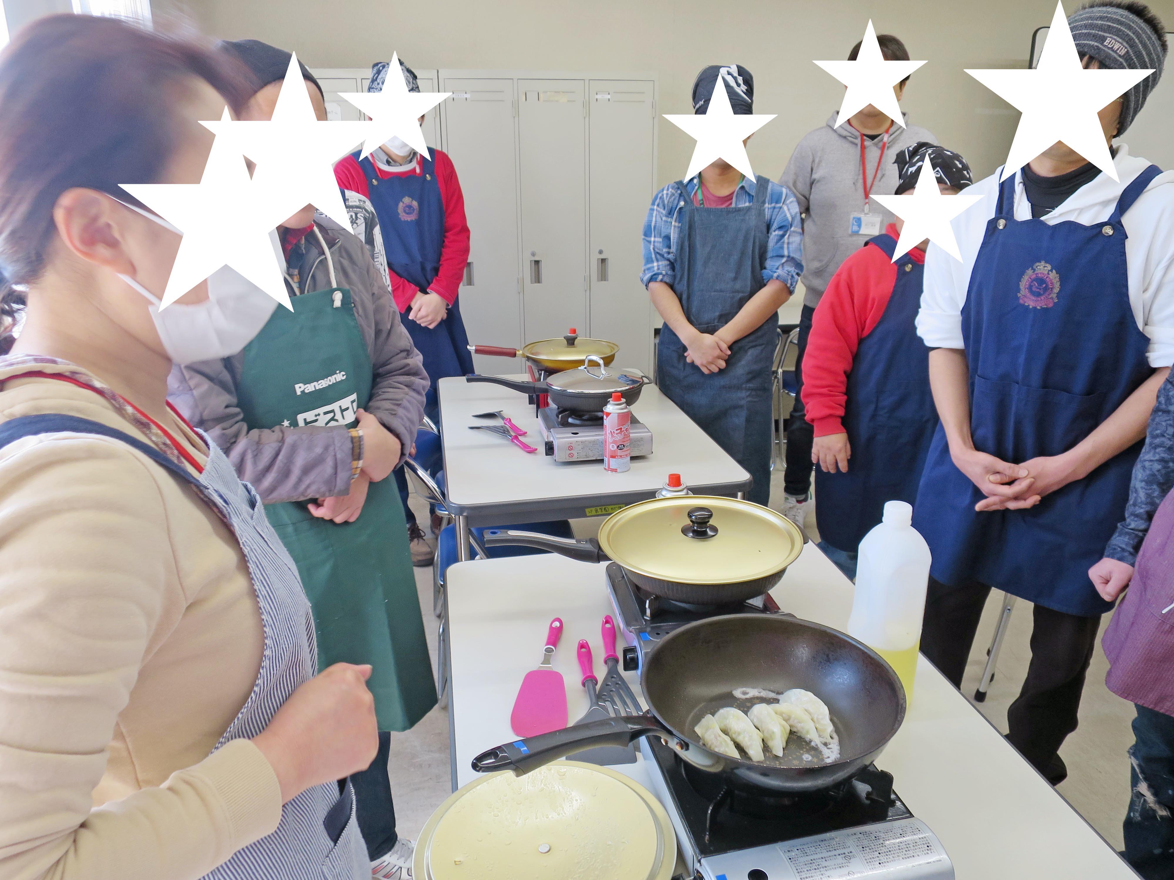 説明を受ける訓練生、写真手前には焼いている最中の餃子