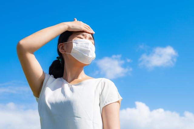 暑そうにしているマスク姿の女性